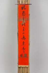 Kakemono con estructura de bambú con tanzaku de caligrafía japonesa en fondo rojo